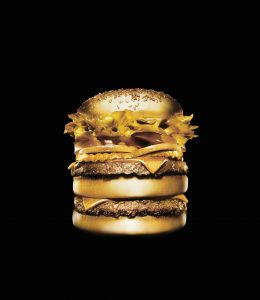 Conceptual still life of a gilded gold hamburger isolated on a black background